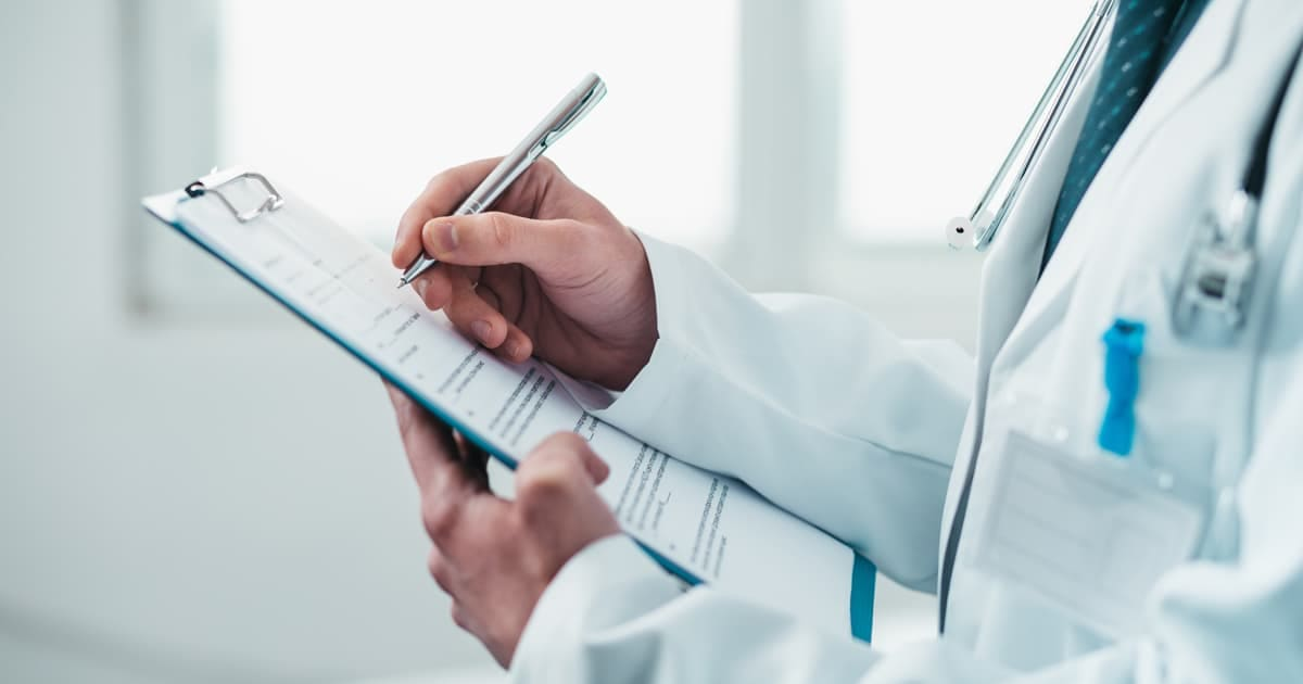 a doctor writing on a clipboard