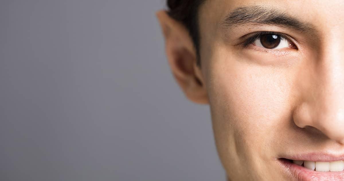 an asian man smiling at the camera