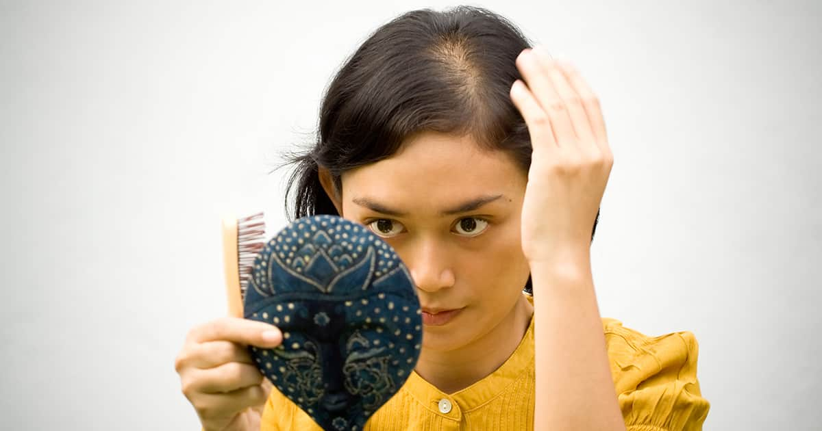 woman with hair loss checking a mirror
