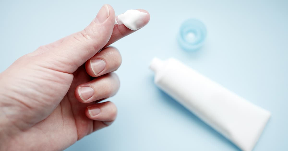 a hand with skin cream on a finger