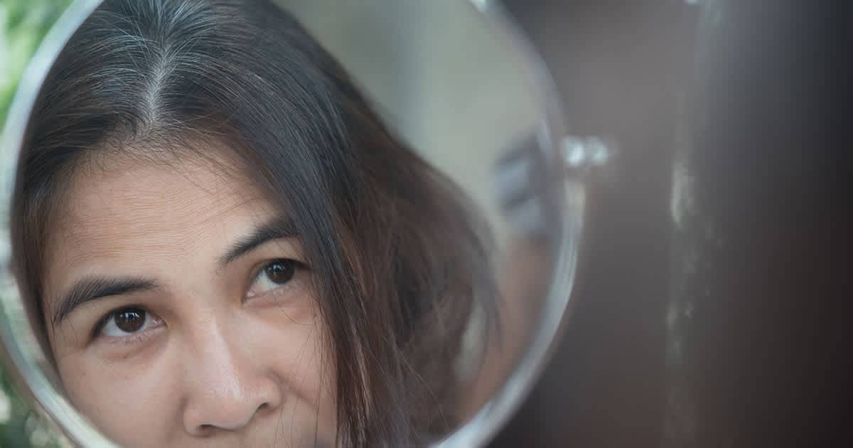 asian woman with hair loss looking in mirror
