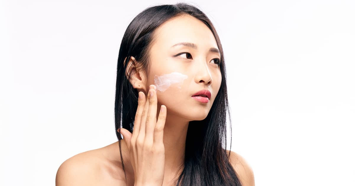 asian woman applying cosmetic cream on face