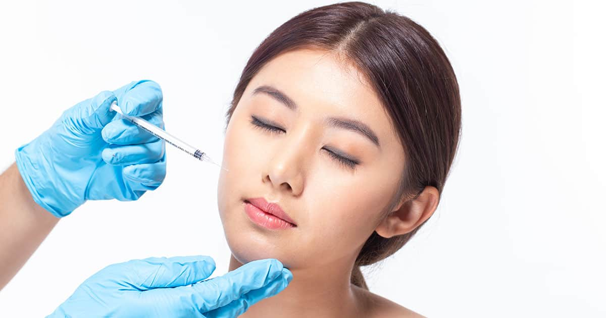 asian woman injecting fillers