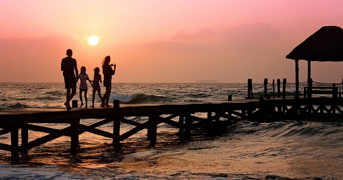 a family with two children walking on a beach boardwalk