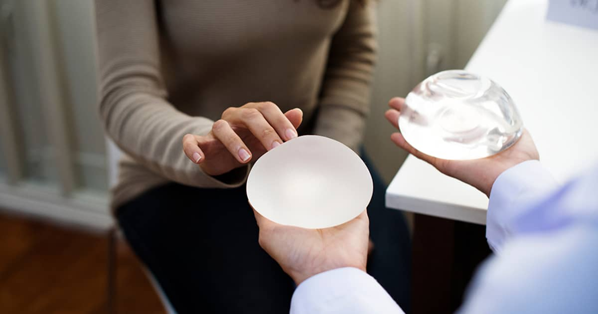 woman choosing between silicone and saline breast implants