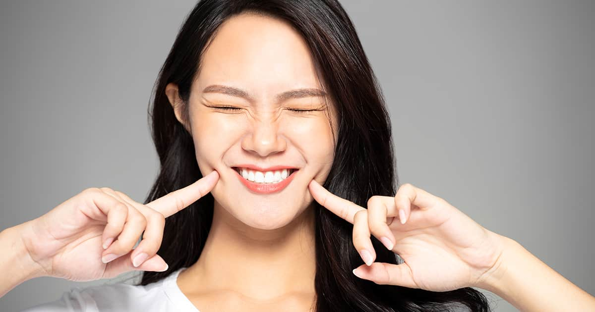 young asian woman smiling with teeth