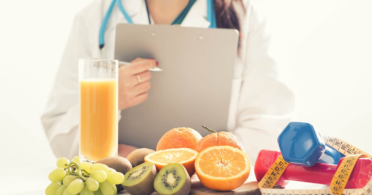 nutritionist with fruits and wellness equipment on table