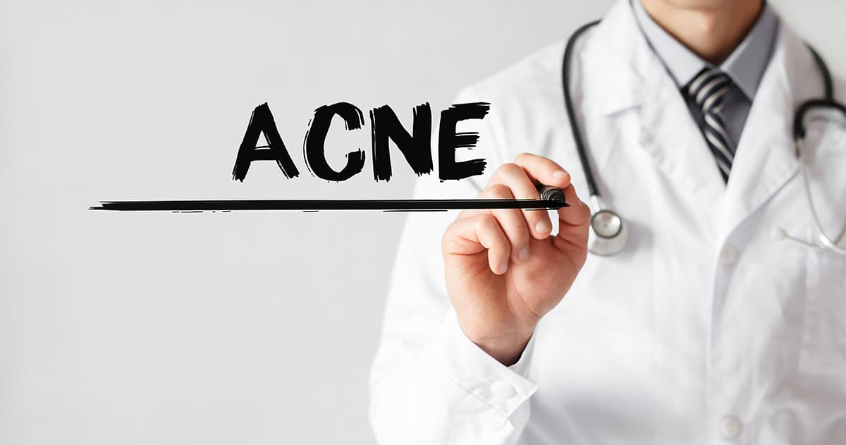 doctor writing the word acne on board