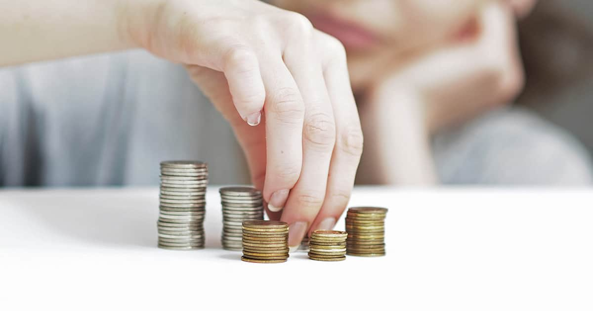 woman stacking piles of coins
