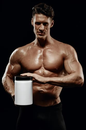 athletic man holding a jar of sports nutrition