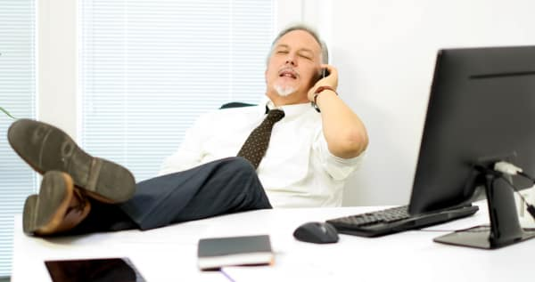 Attractive business man leaning back in chair, with legs on desk while chatting on the phone.