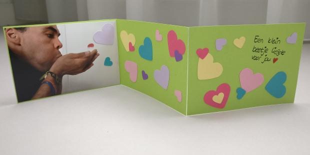 Drieluik kaart met persoon die hartjes wegblaasd en aan de rechterkant staat nog een lieve teskt.
