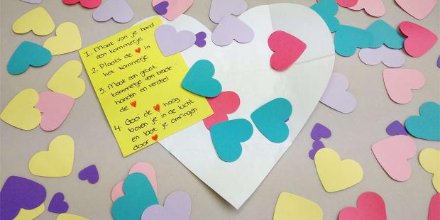 Geopende enveloppe met allemaal hartjes confetti eromheen en bovenop liggen de instructies.