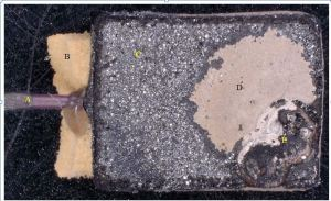 The capacitor after plastic was removed, E is the failure site
