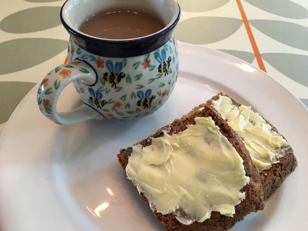 Mug of tea with slices of buttered walnut and date loaf