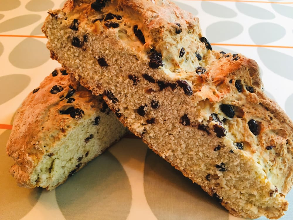 Fruited white soda bread cut in half on a table
