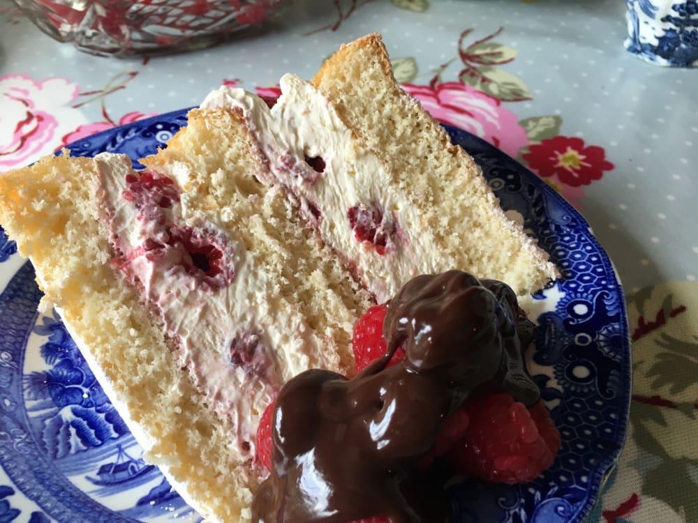 Slice of raspberry cream sponge served with fresh raspberries and a chocolate sauce