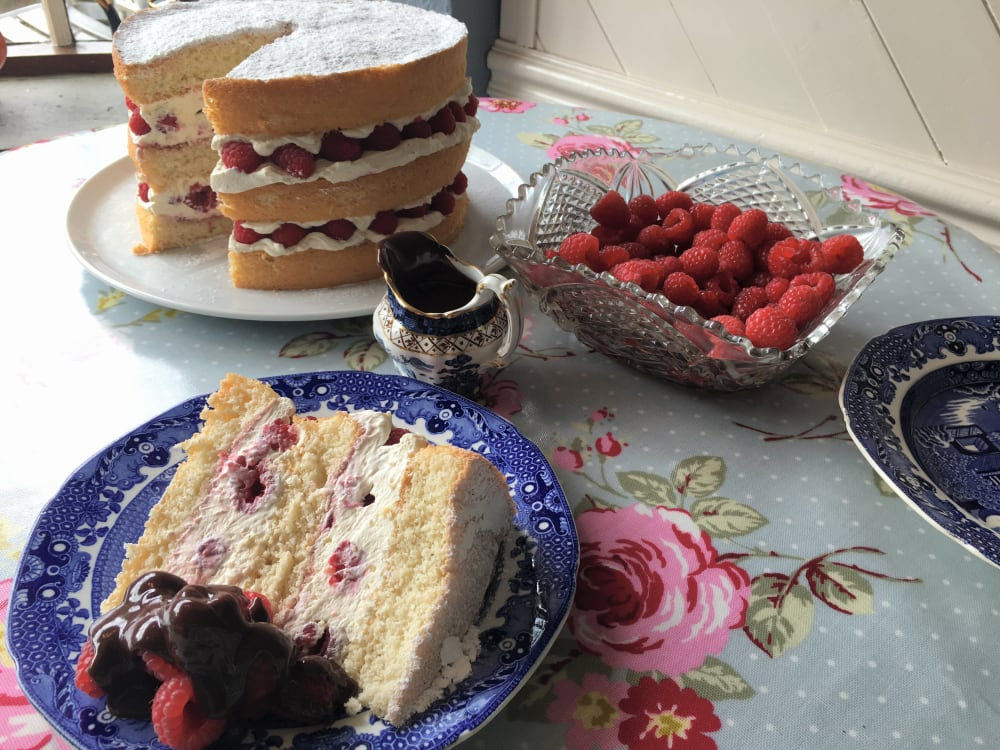 Slice of raspberry cream sponge on a plate with a bowl of fresh raspberries, jug of chocolate sauce and the full sponge in the background