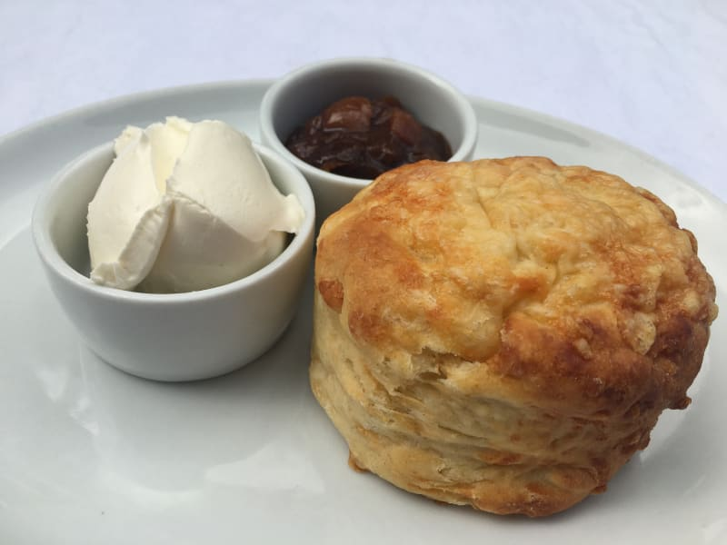 Cheese scone on a plate with chutney and cream cheese