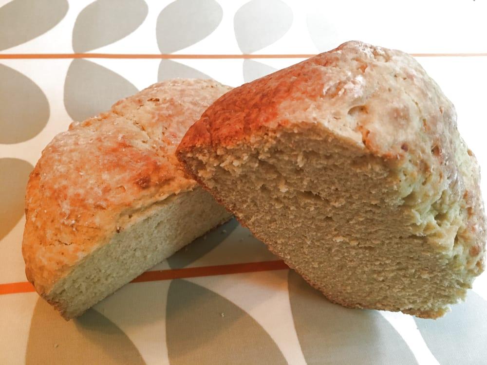 White soda bread cut in half on table