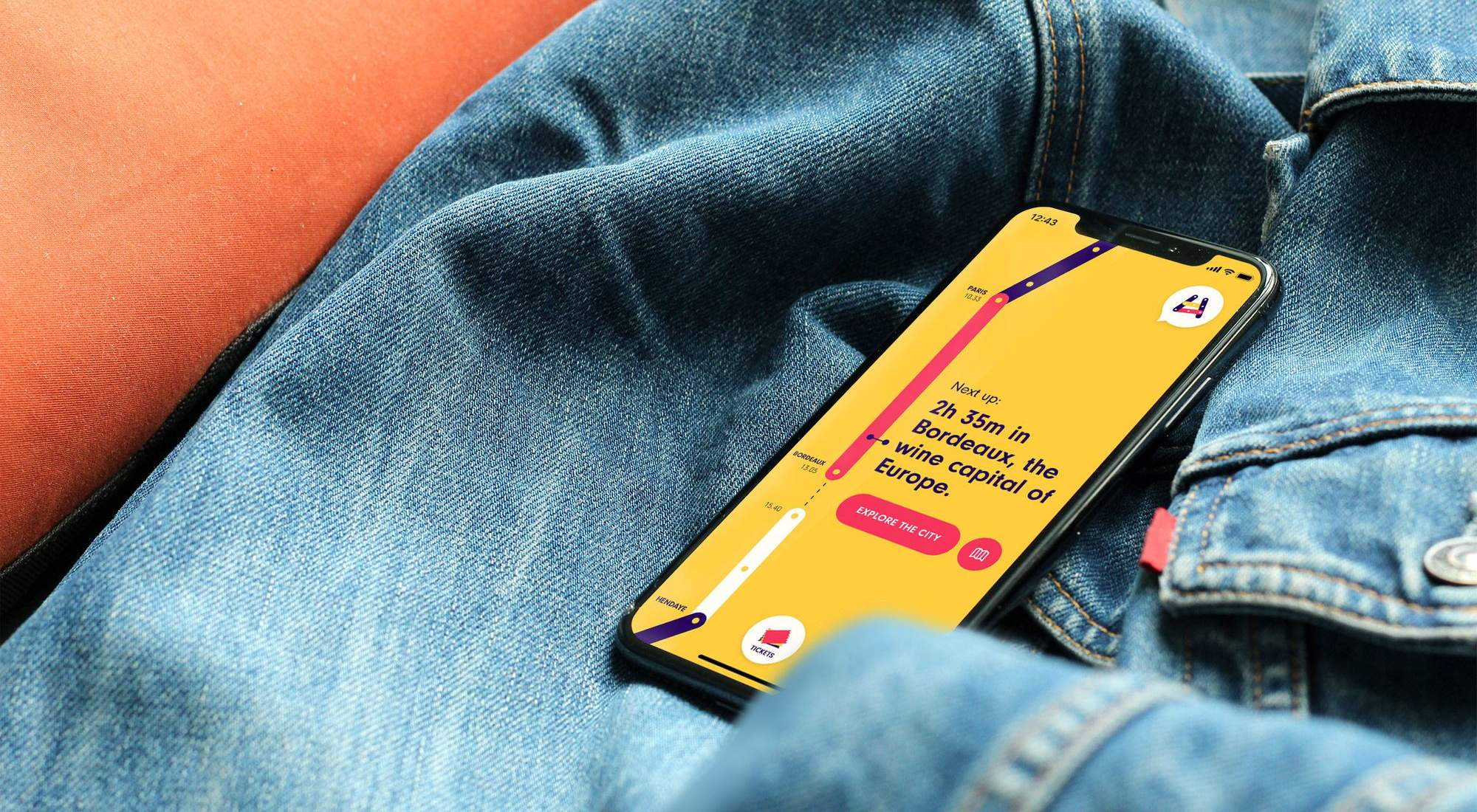 A smartphone laying on a jeans jacket with the All Aboard app open