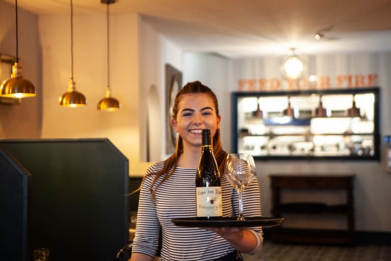 Front of house team member serving wine
