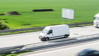 White delivery van driving down the highway