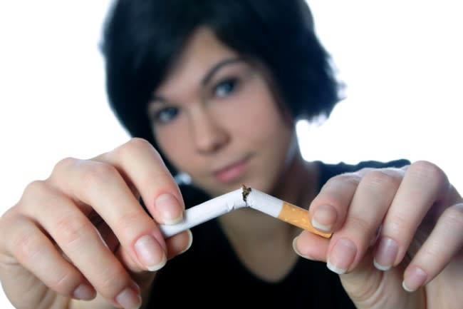 Young woman breaking cigarette.Isolated on white.