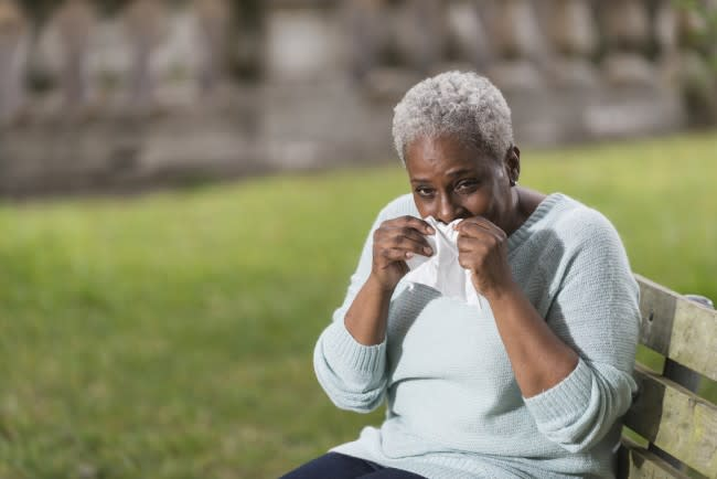 Senior black woman holding tissue to her nose