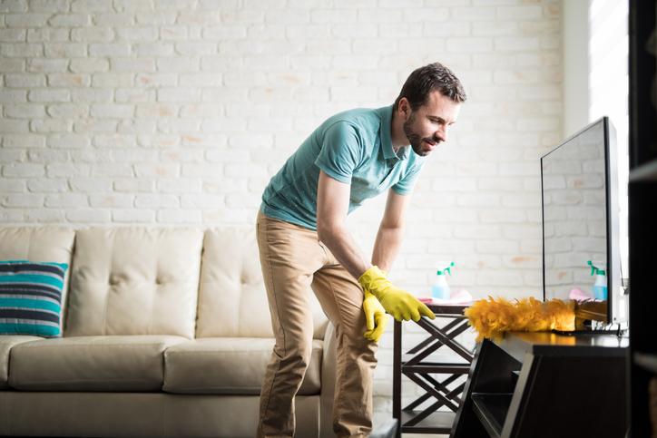 man dusting in home