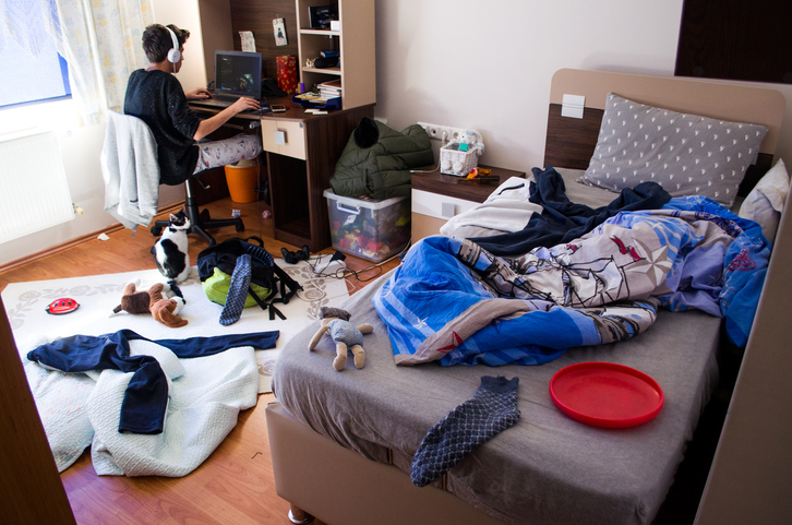 student studying in messy dorm room