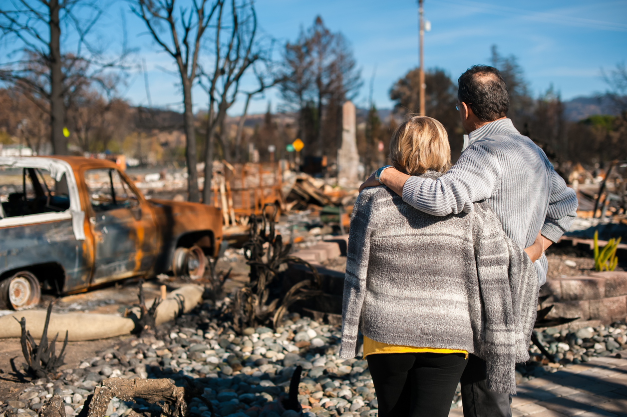 couple looking at home destroyed by wildfire
