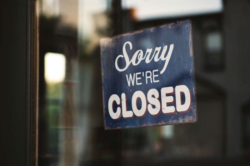 """Vitrine de loja com o sinal dizendo """"Sorry, we're closed"""""""