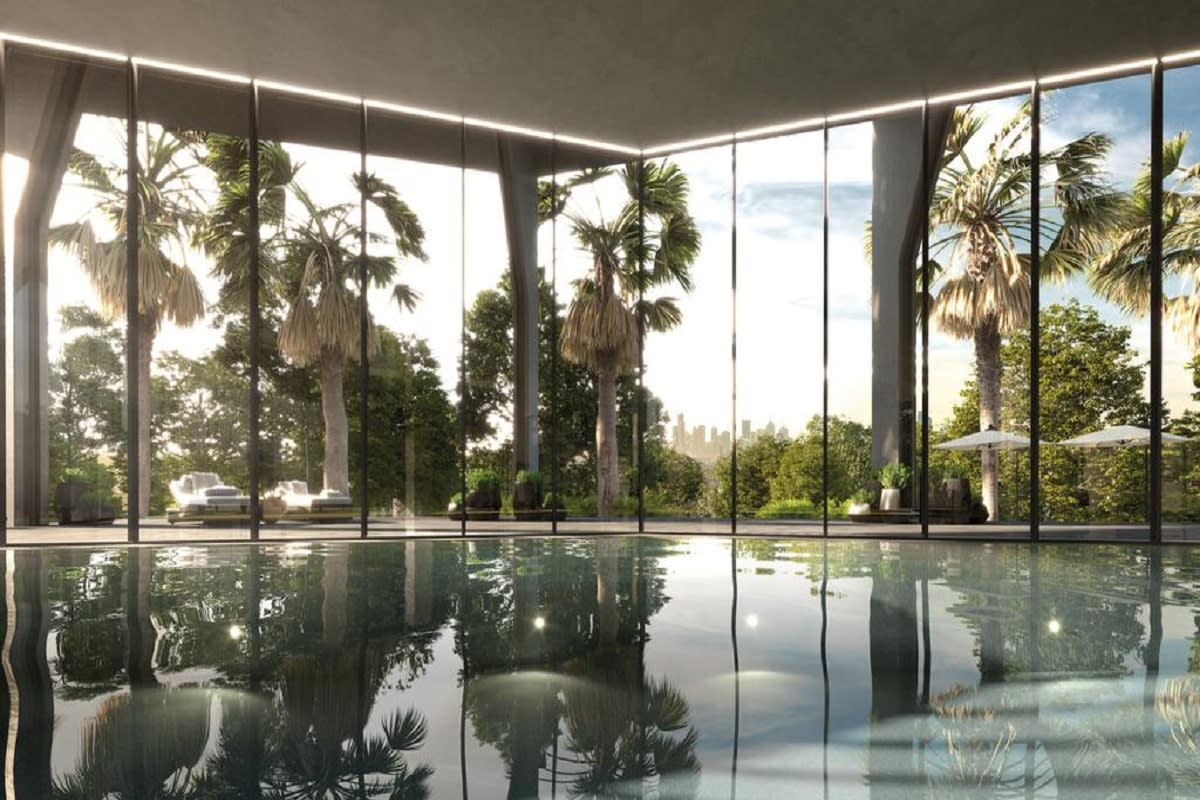 The tranquil communal pool with surrounding greenery and city skyline view.