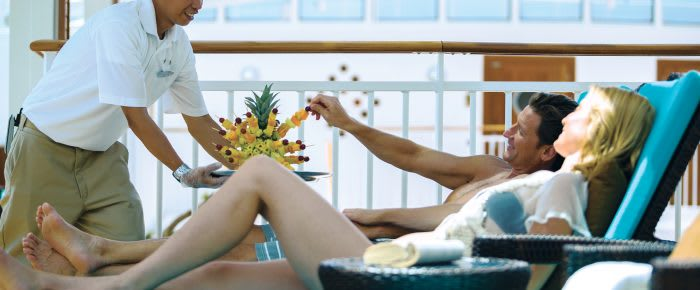 Couple having a drink on pooldeck onboard a cruiseship