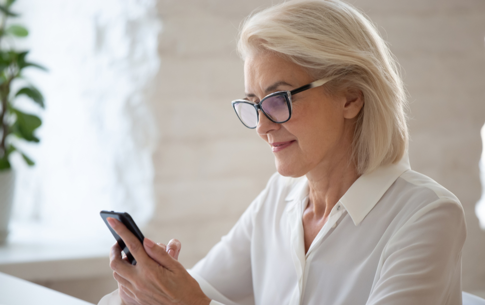 A woman wearing blue light blocking reading glasses looking at a phone