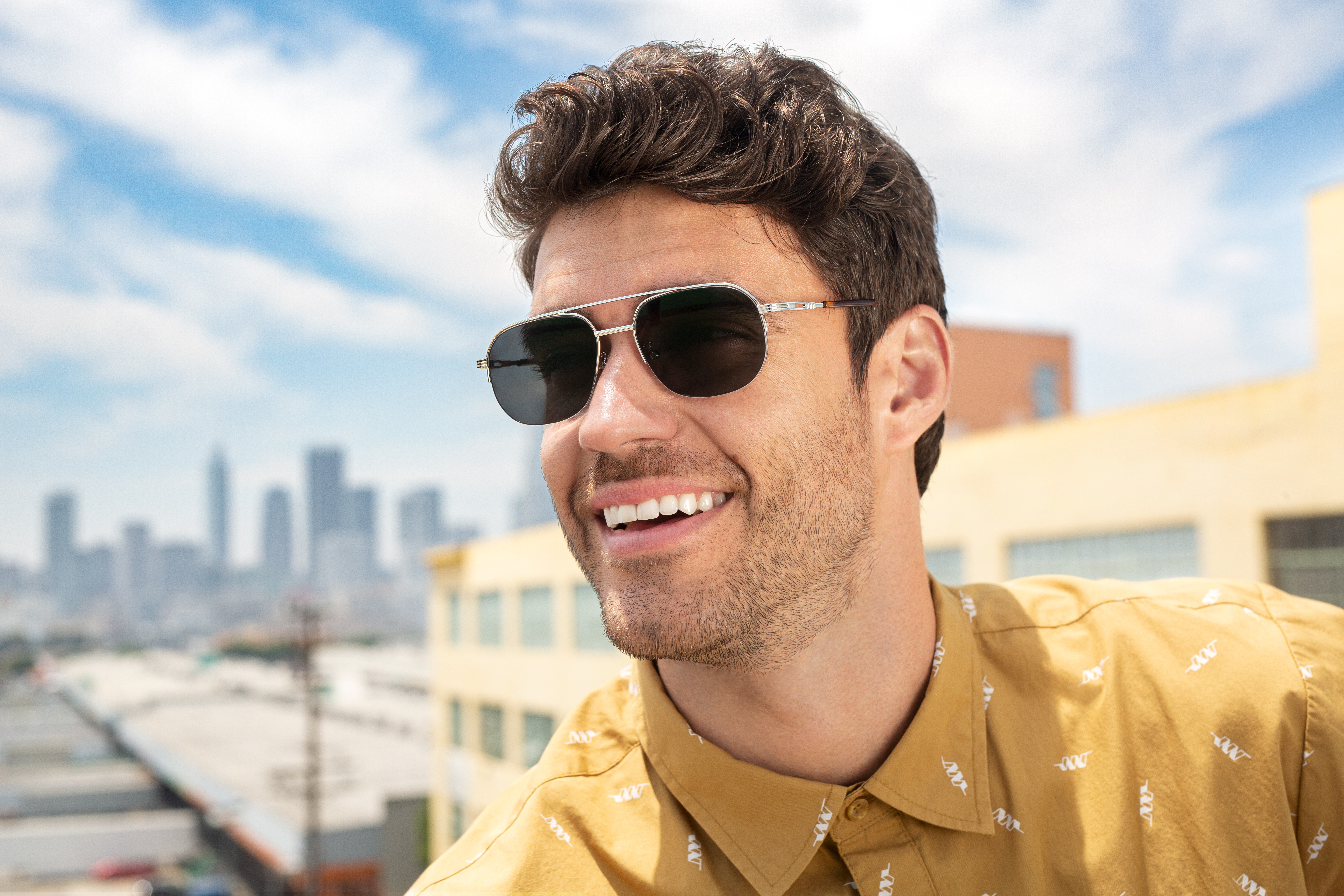 A man wearing prescription sunglasses with a city in the background