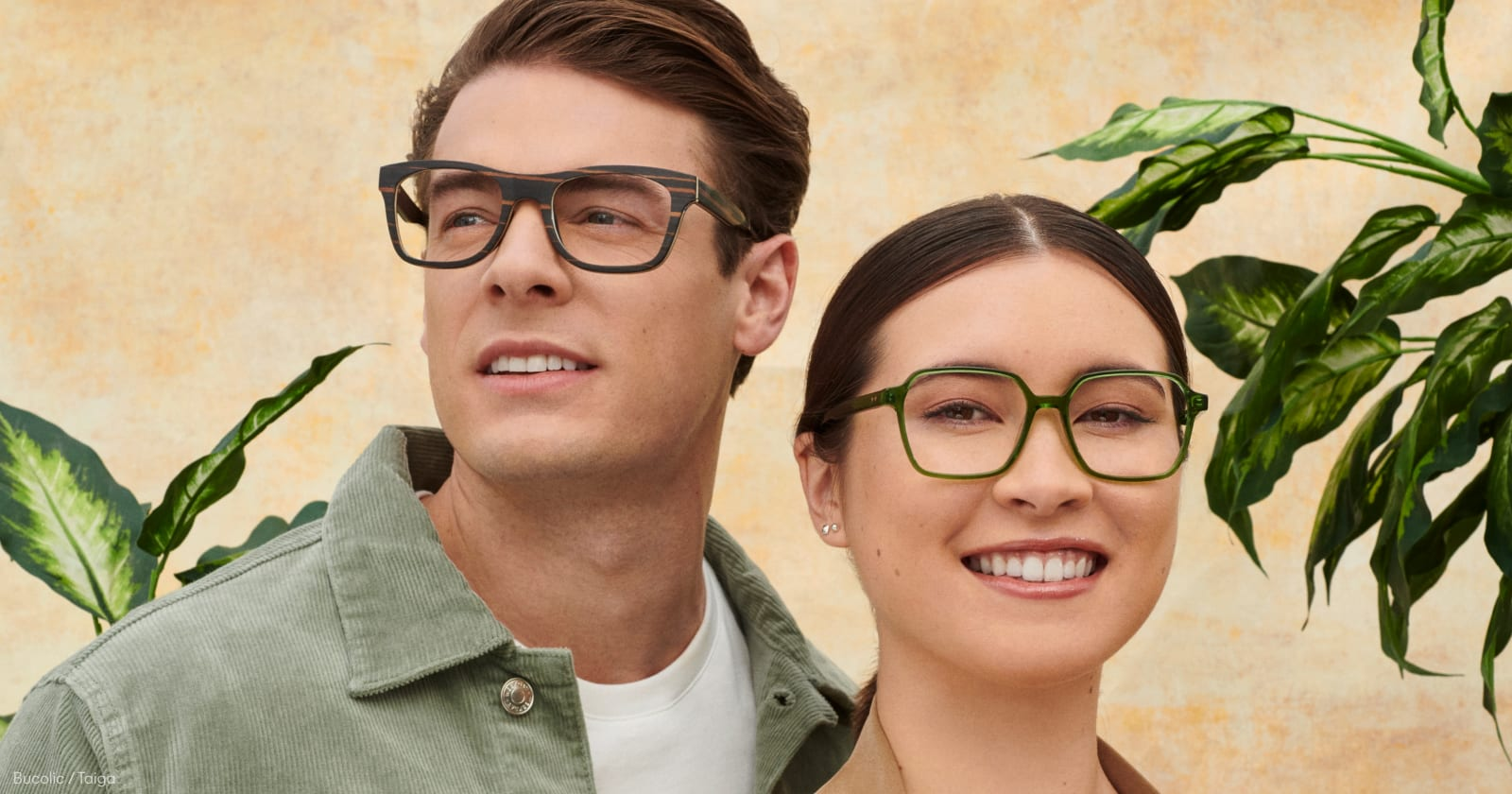 A man and woman wearing glasses in front of a yellow wall