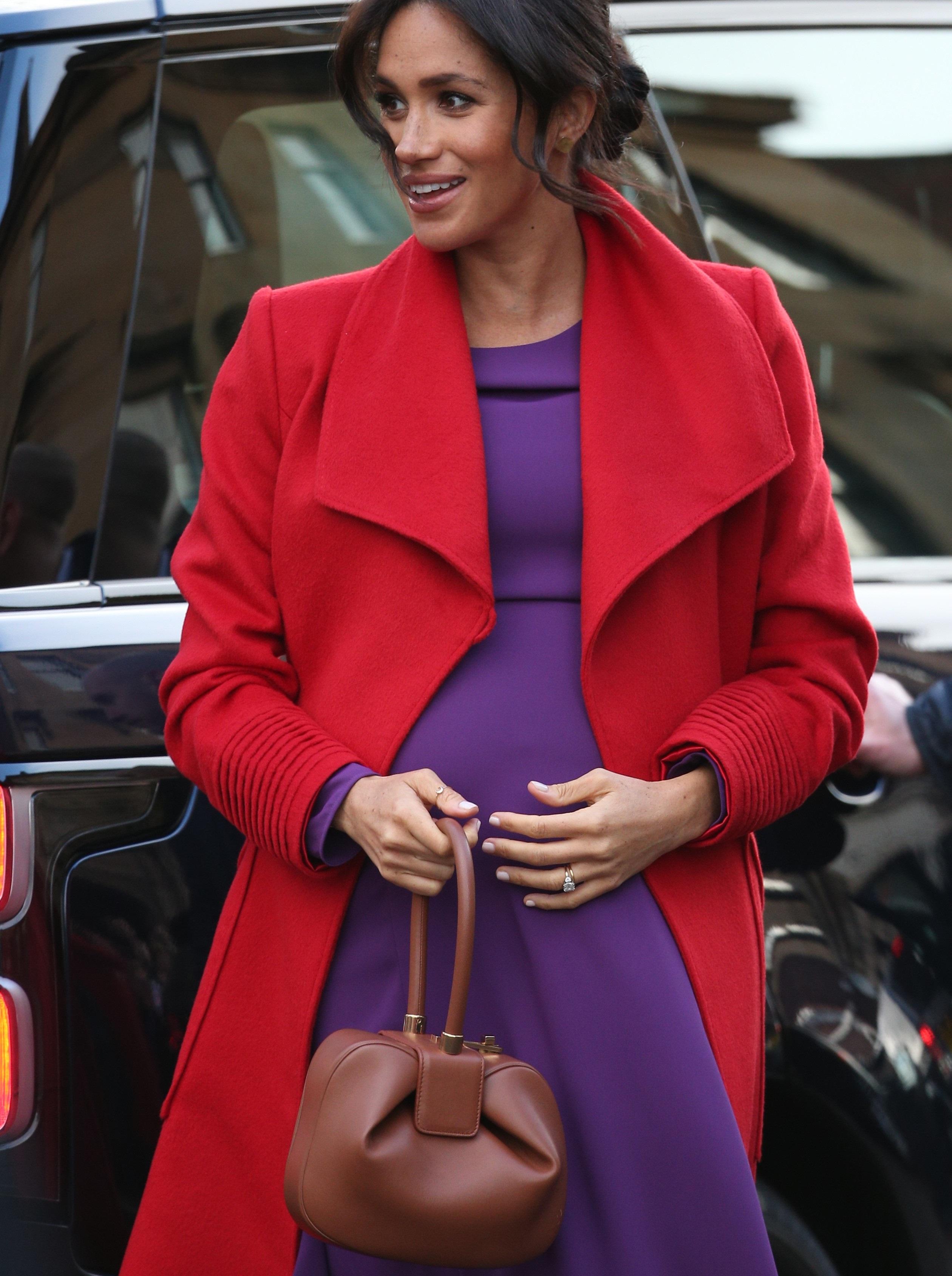 Meghan Markle usando casaco vermelho e vestido roxo, para ilustrar o color blocking