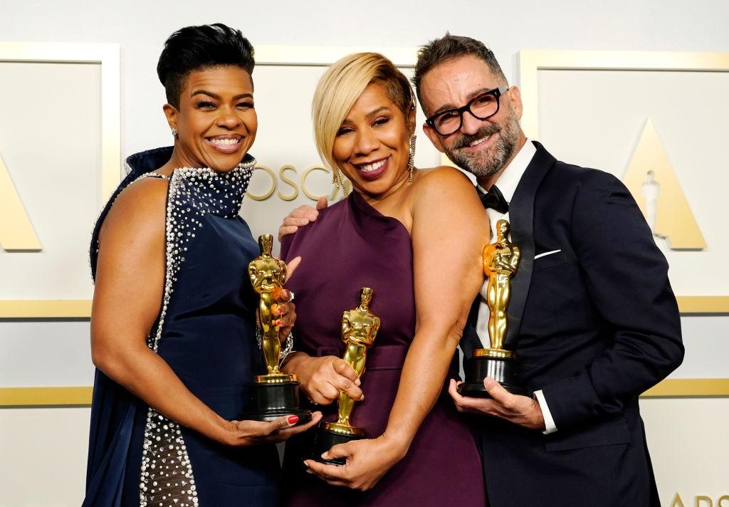 homem e duas mulheres negras inspiradoras segurando estatueta do oscar