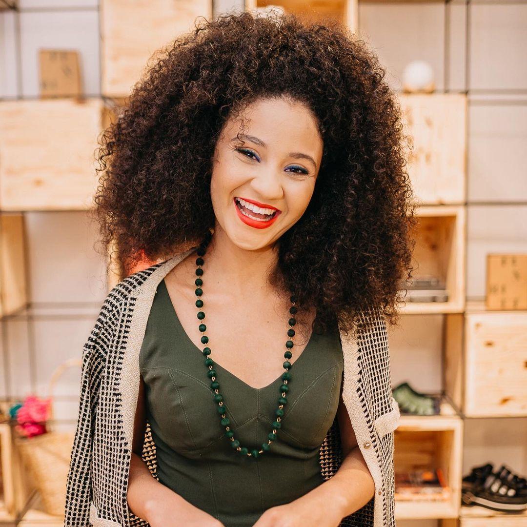 mulher negra sorrindo de pé em uma sala