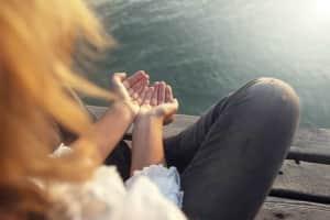 Meditation hand gesture on a boardwalk