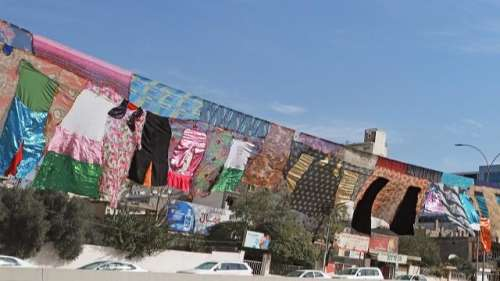 Iraqi artist spotlights domestic abuse survivors with wall of clothes