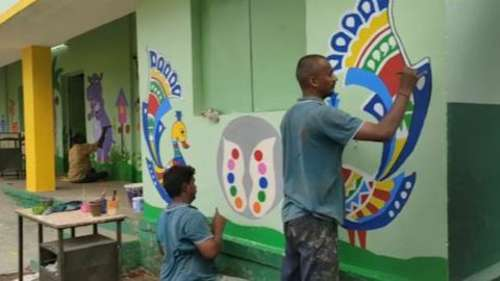 Teachers paint colourful artwork in schools to encourage admissions