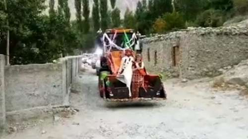Newlywed couple in Pakistan arrive in village riding an excavator