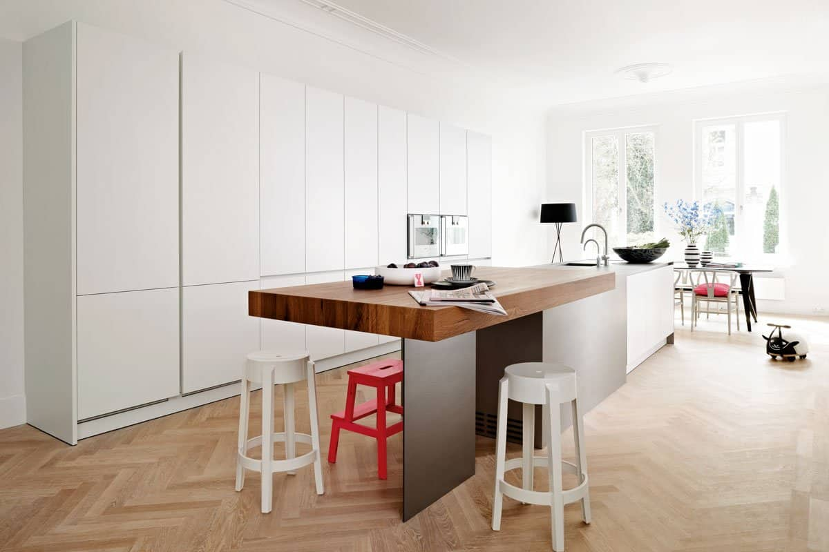eggersmann designed kitchen in matte white with warm wood breakfast table built into island