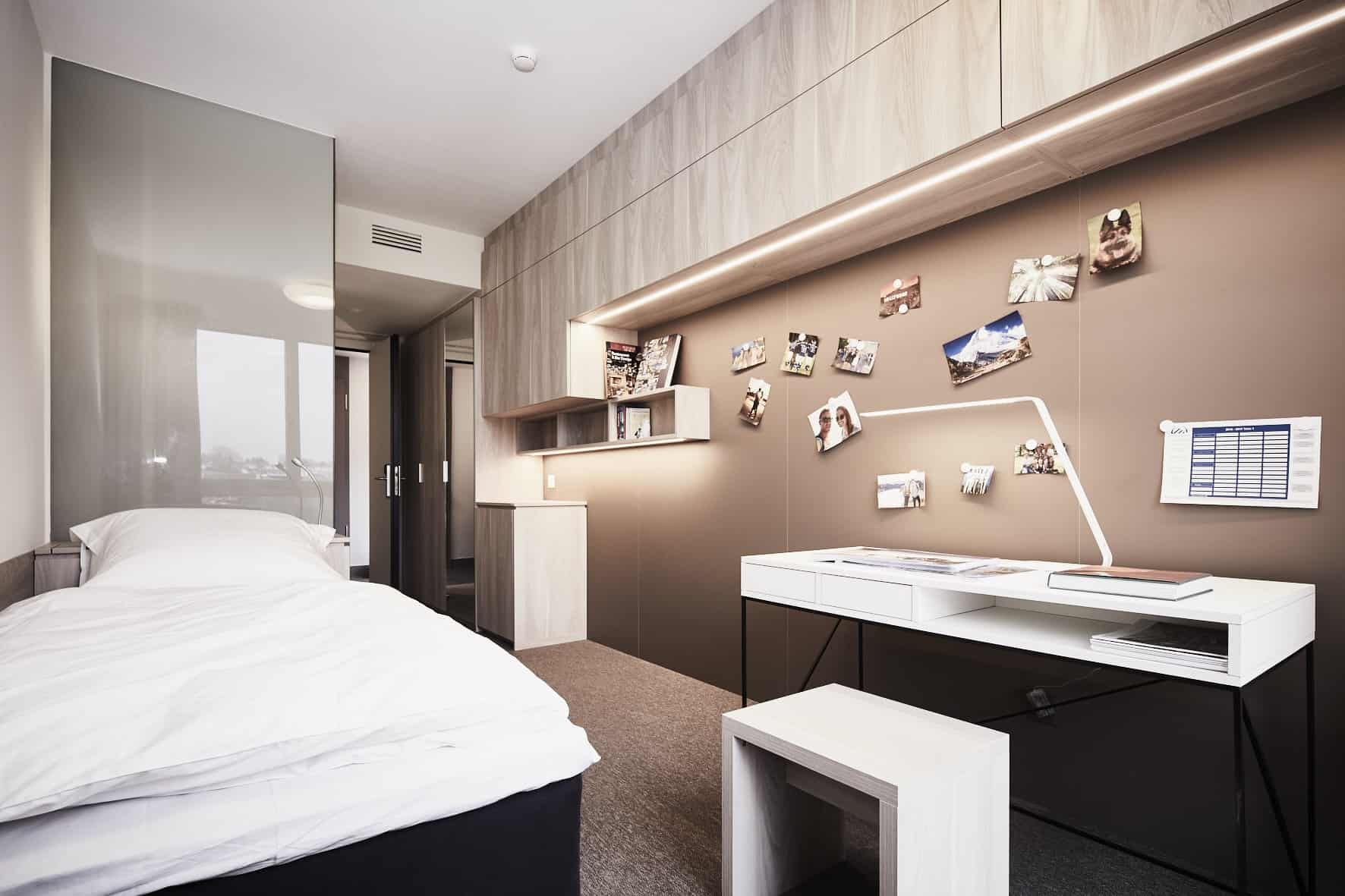 a warm palette and clever hideaway storage keep this hard-working bedroom with cantilevered office desk looks luxurious