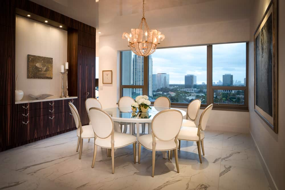 custom dining room buffet flanked by floor-to-ceiling storage cabinets in makassar veneer set off by white upholstered chairs and luxuriously detailed dining room table all designed by eggersmann