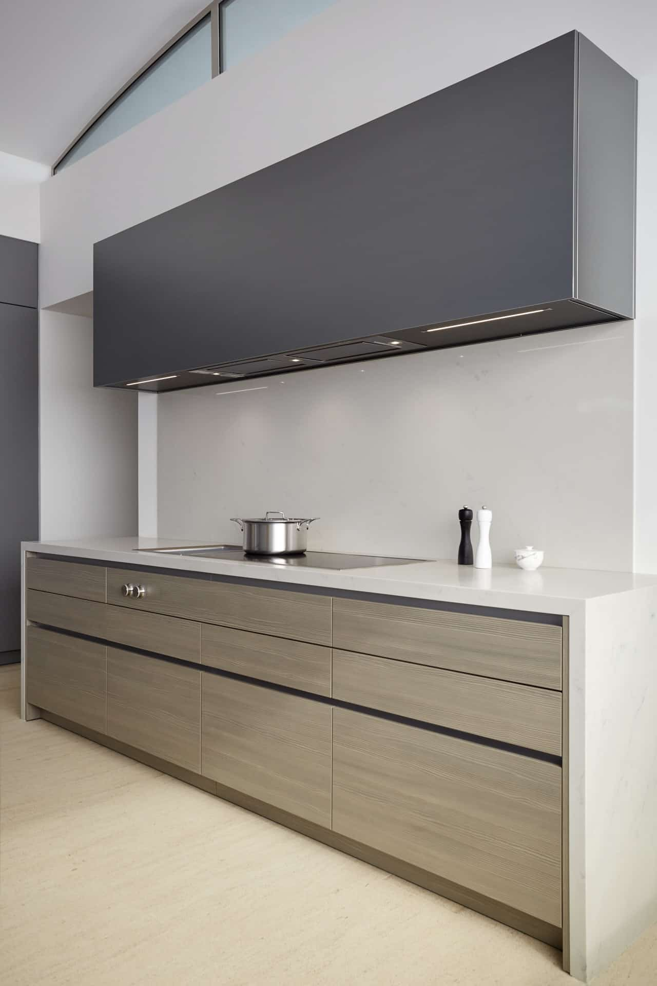 Main kitchen's induction stove and beautifully paired cabinetry finishes in woodgrain laminate and dark aluminum