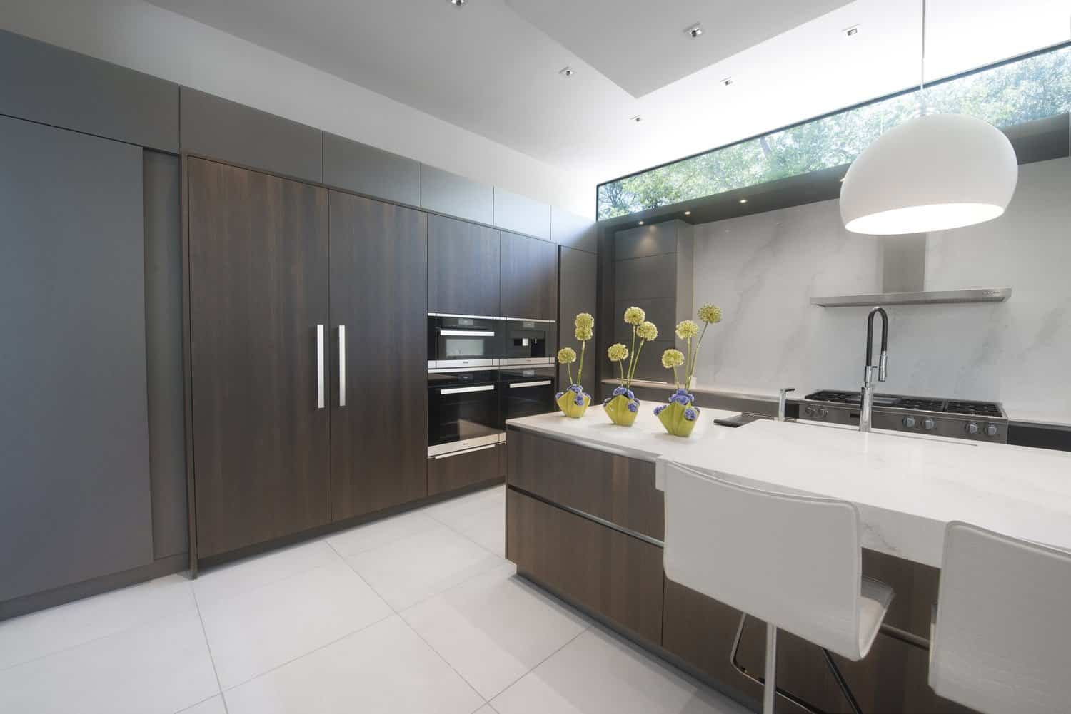 integrated subzero refrigerator and bank of miele appliances are convenient to the expansive countertop with breakfast bar